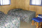 The first bedroom in Cabin #12 has two double beds.