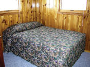 The first bedroom in Cabin #15 has a double bed.
