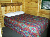 The Master Bedroom in Cabin #7 has a log headboard.
